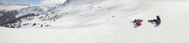 Snowboarders in open snow field mid-run