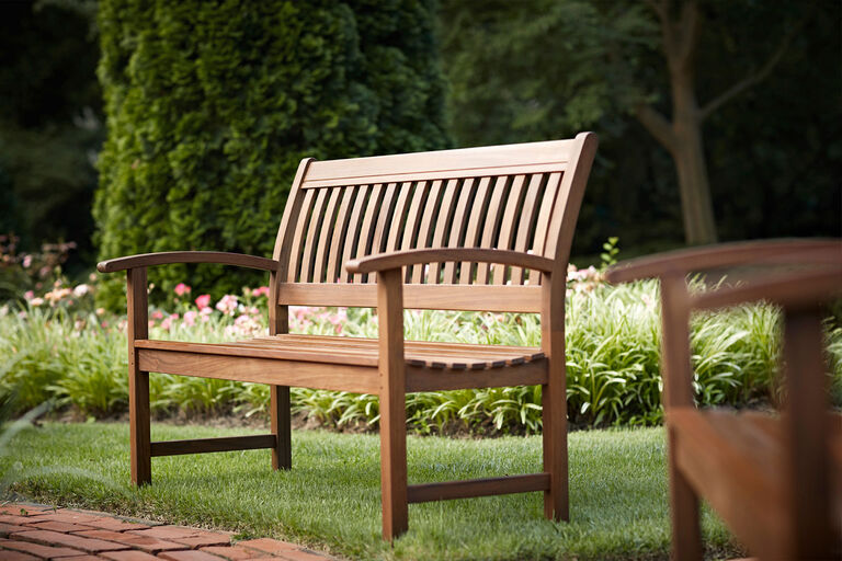 Classic Ipe bench by Jensen Outdoor in lush backyard
