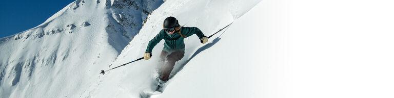 Downhill skier on steep terrain in deep powder