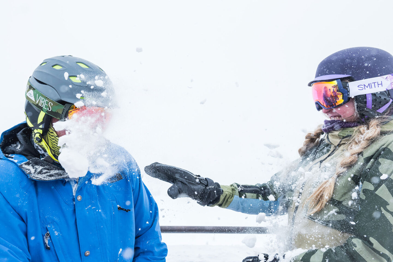 woman playfully throwing snowball at man wearing ski helmet and ski goggles