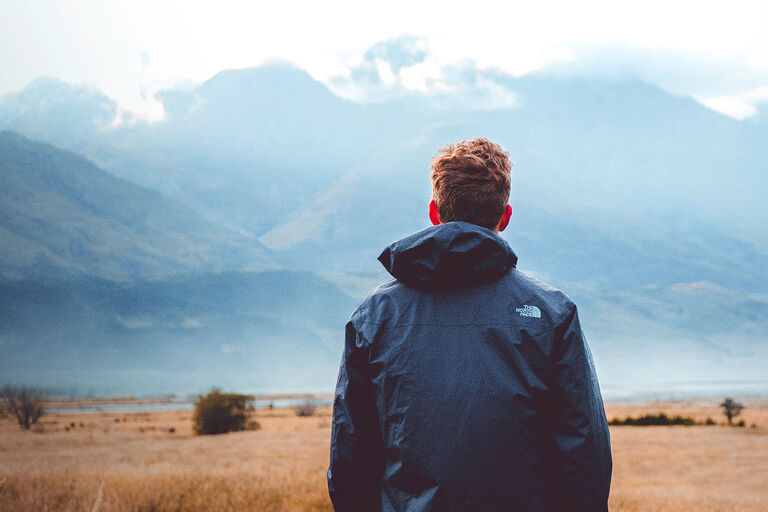 Man looking off into distance at mountains in a winter jacket