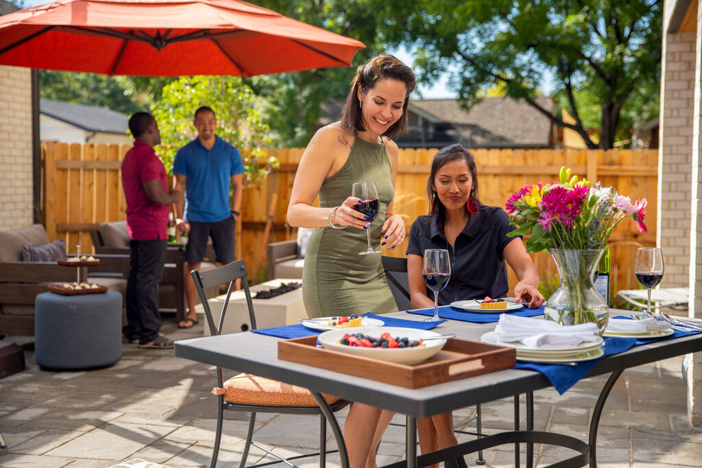 People enjoying being outdoors in their backyard with patio furniture and umbrella
