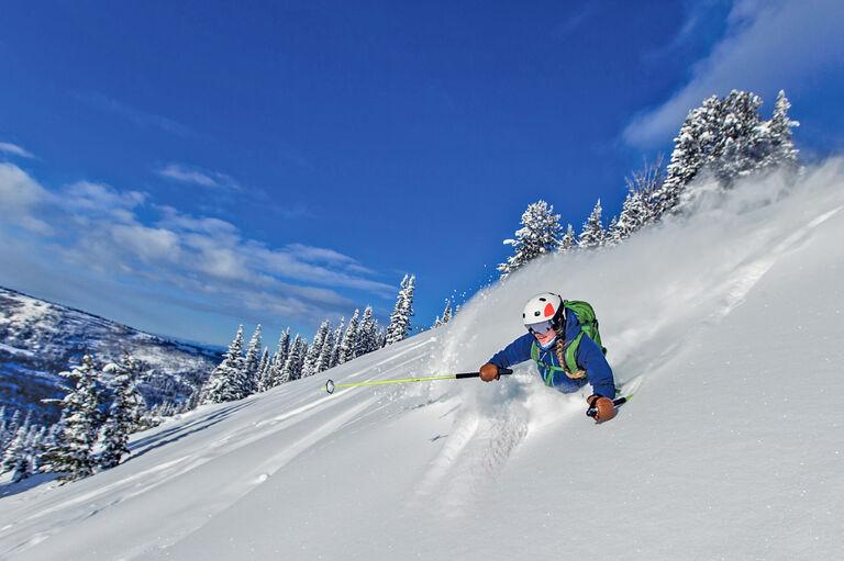 Skier in deep powder with blue skies