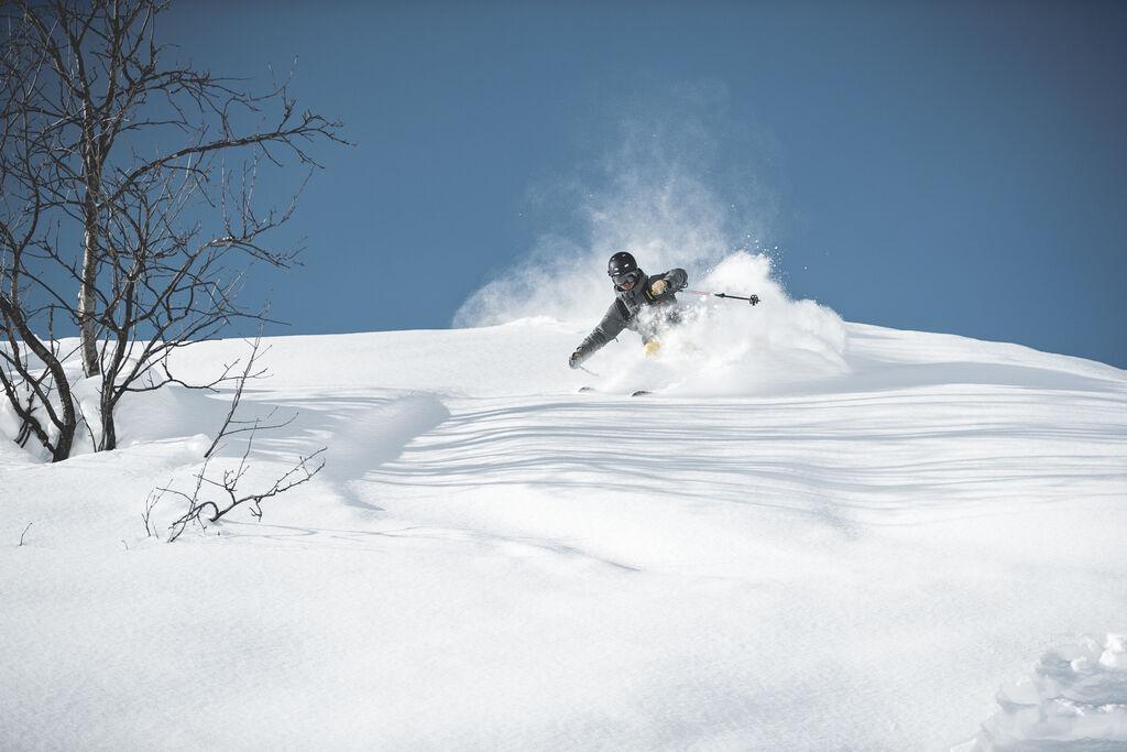 Male skier slashing fresh powder on a bluebird day