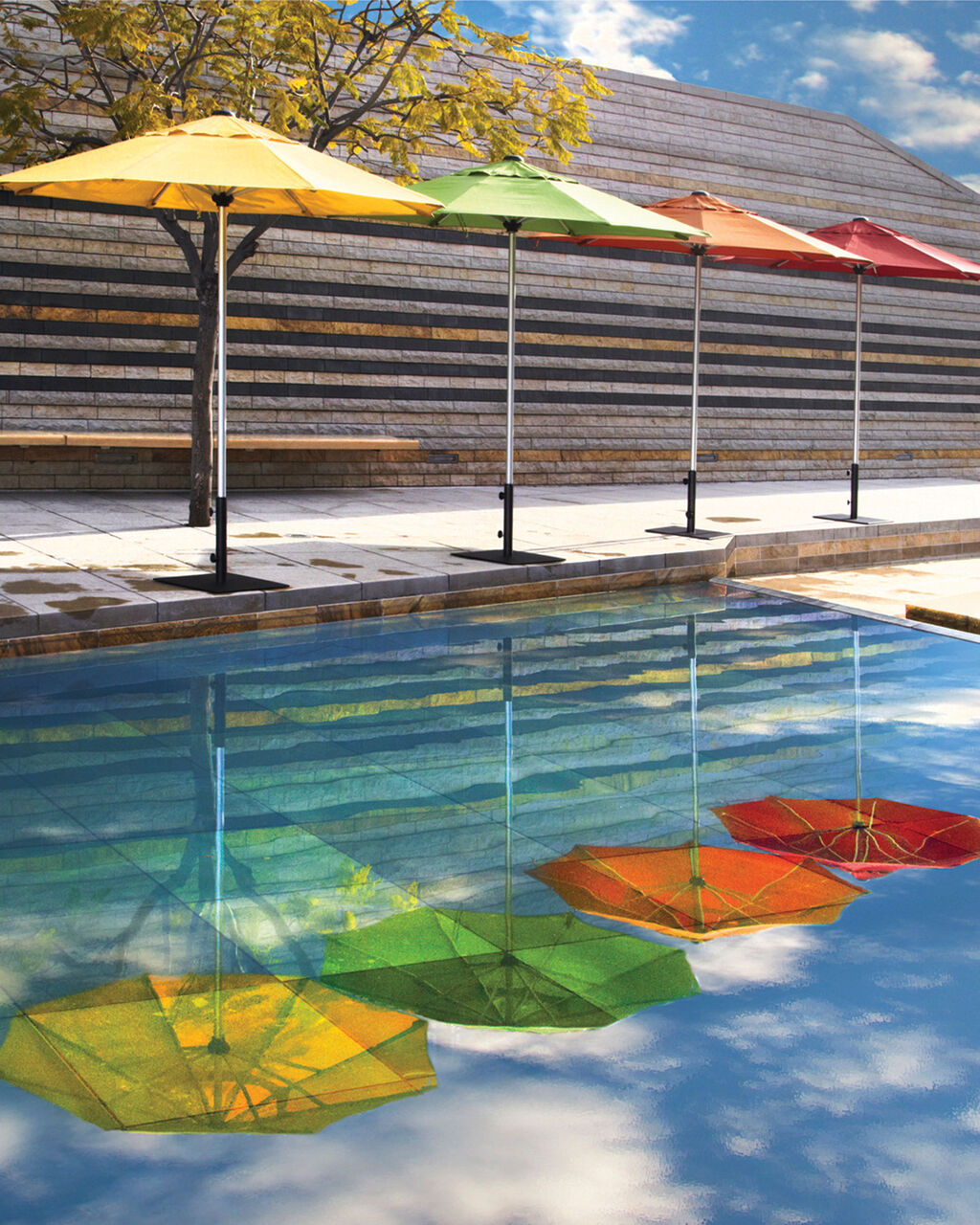 Colorful commercial patio umbrellas next to pool