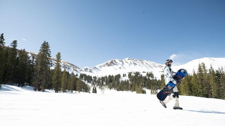 Snowboarder walking with board