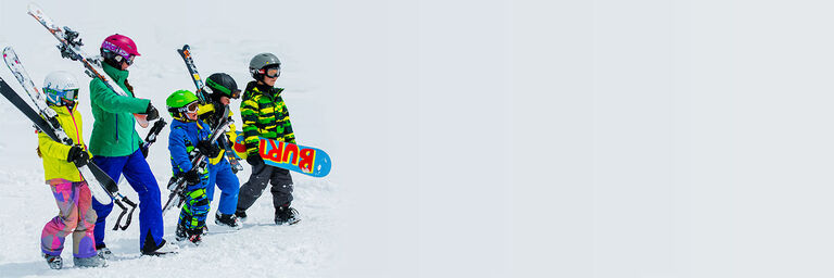 family on top of mountain with ski and snowboard rental gear