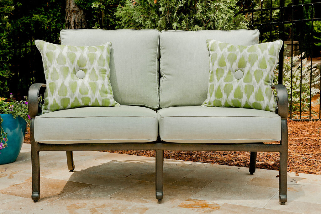 Durable gray and green outdoor cushions & pillows on a loveseat