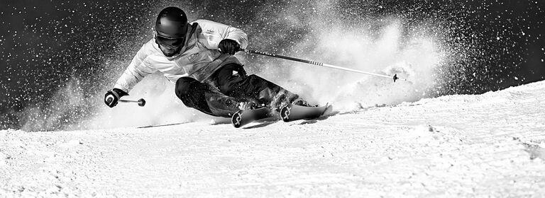 Skier carving through snow