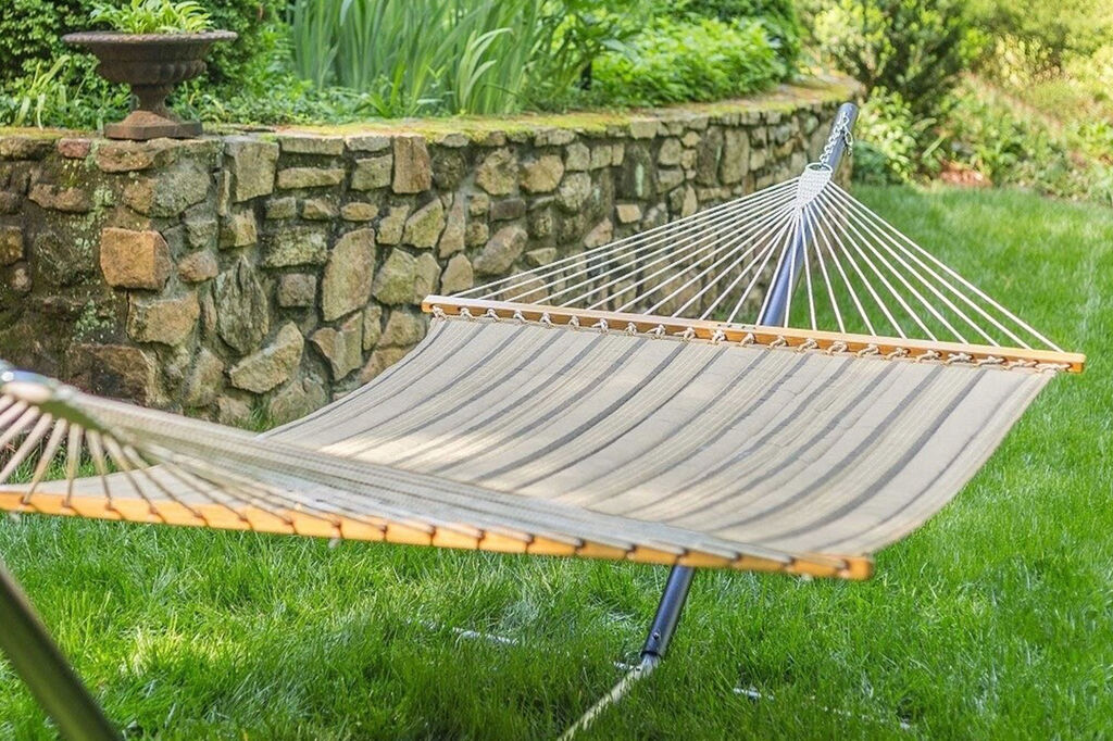 Padded hammock in backyard on bright green grass