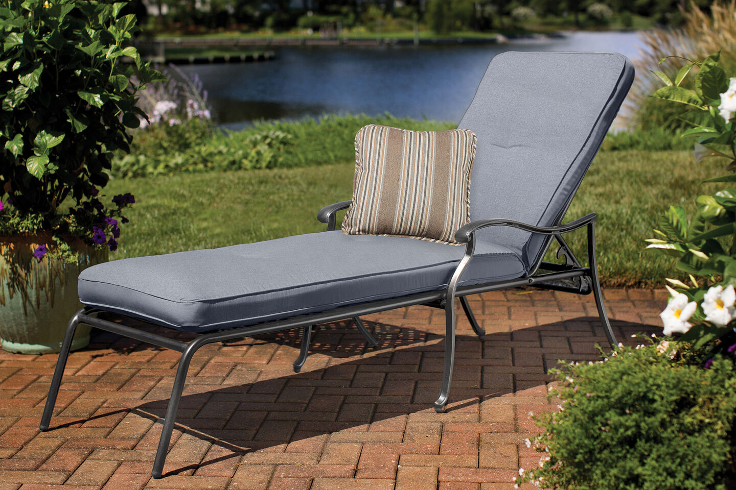 Madison by Aty chaise lounge with blue cuspricihion and striped accent pillow on brick patio