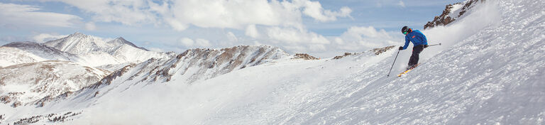 skier dropping in above tree line