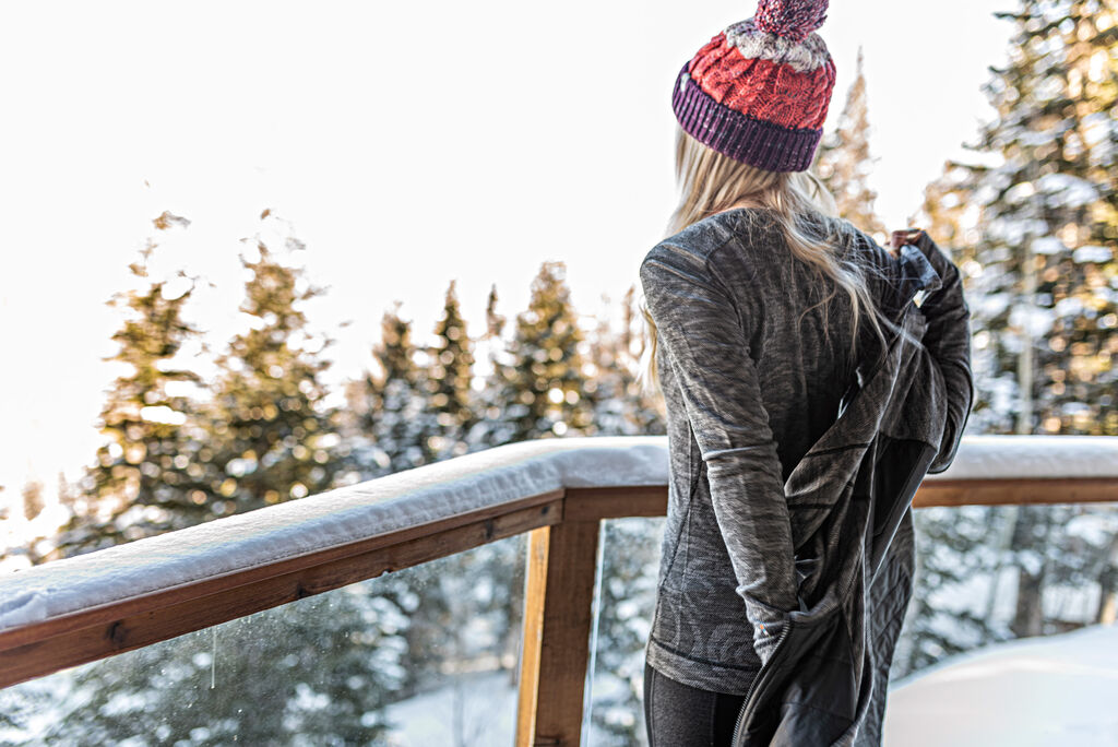 Woman in Smartwool baselayers on snowy balcony