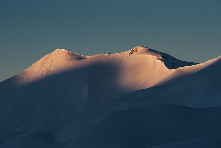 Mountain peaks with ski tracks through freshly fallen snow
