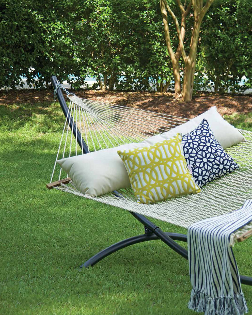 Woven hammock in the lawn under shade from surrounding trees