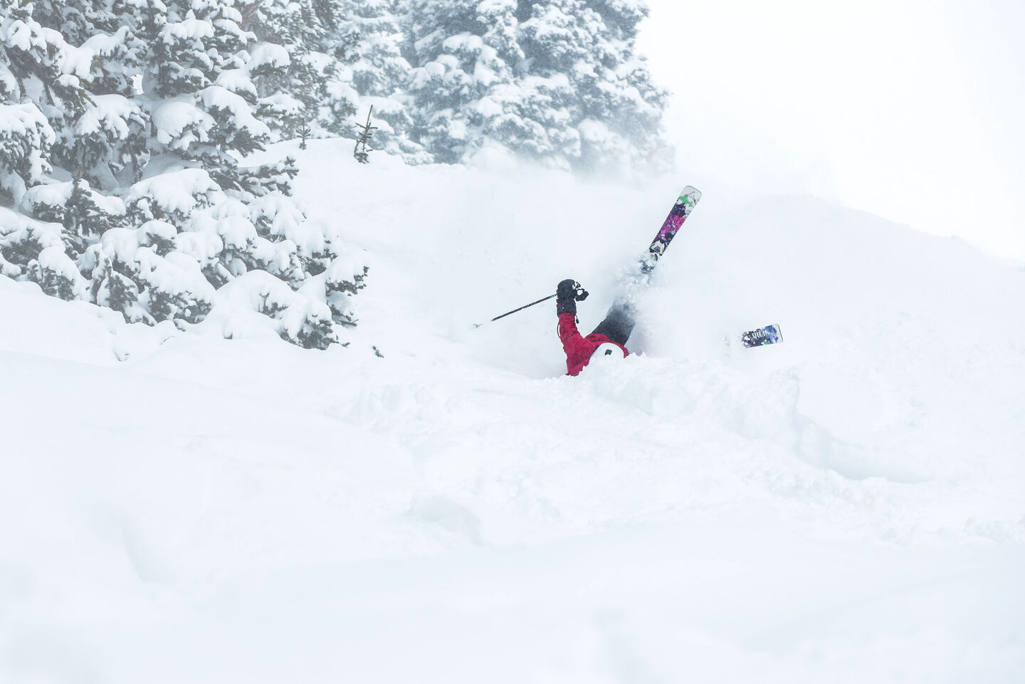 Skier wiping out in deep powder