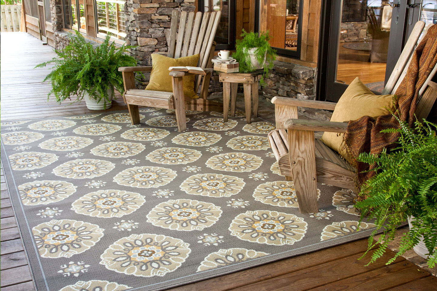 Outdoor rug with two Adirondack chairs on a covered patio