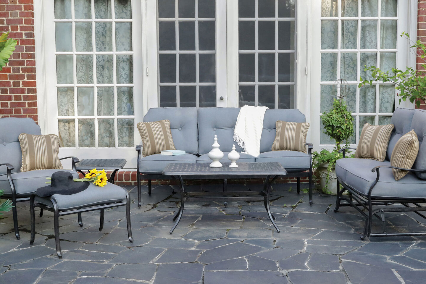 Madison by Apricity lounge furniture with coffee table on gray stone patio