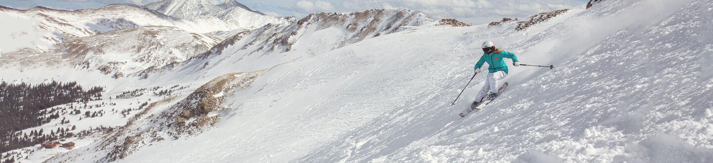Skier in an open run above tree line