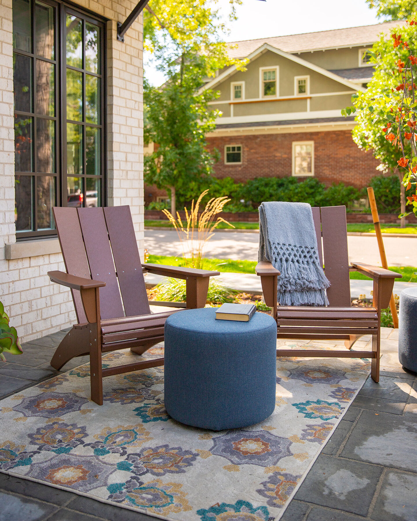 Two brown Adirondack patio chairs made of recycled materials by Polywood accented by a pool stool on an outdoor rug