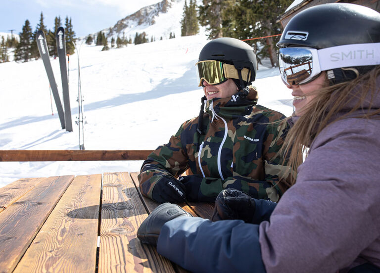 Skiers in helmets taking a break at a picnic table