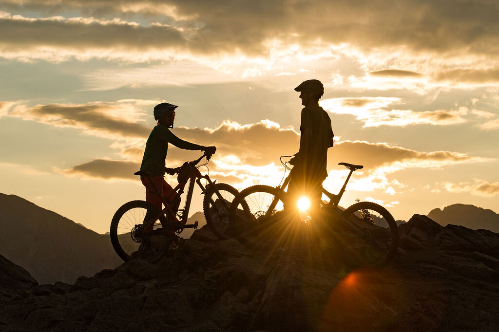 two mountain bikers enjoying the sunset after their summit